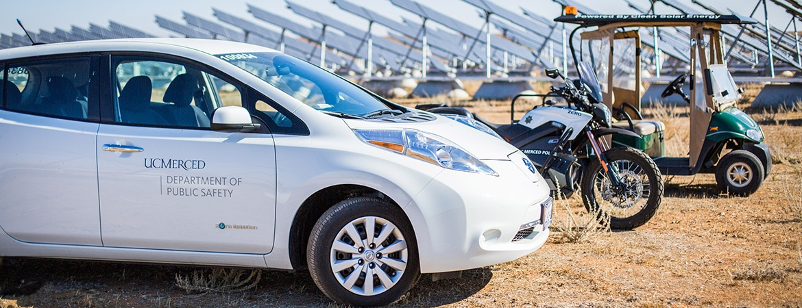 Image of university vehicles parked by solar array